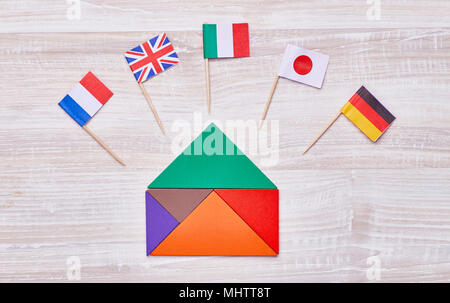 A colored house, assembled from geometric figures, with flags of different countries. Concept for language courses, translators, etc. - Stock Photo