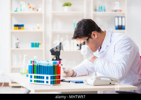 Young chemical scientist working in lab - Stock Photo