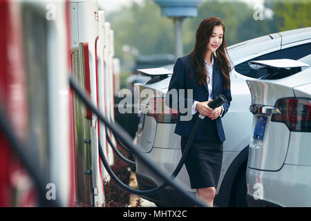 Young business woman to recharge electric cars - Stock Photo