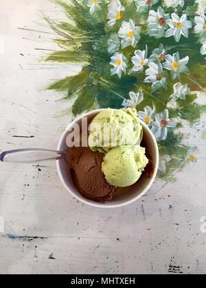 Selection of gourmet flavours of Italian ice cream in vibrant colors served in individual plastic tubs on an old rustic wooden table in an ice cream p - Stock Photo