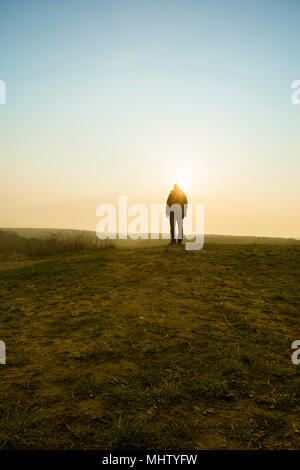 Rear view of a male figure standing on the field at sunset - Stock Photo