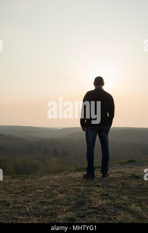 Rear view of a man standing on top of the mountain - Stock Photo