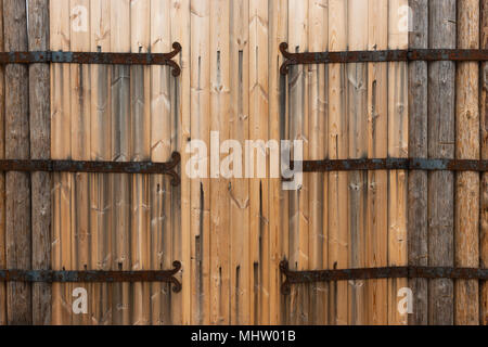 Details of a wooden gates of an ancient fort or fortress with six grunge metal hinges covered with a thick layer of rust - Stock Photo