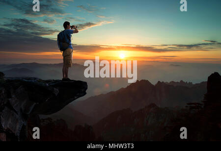 The middle-aged man standing on the cliff overlooking - Stock Photo