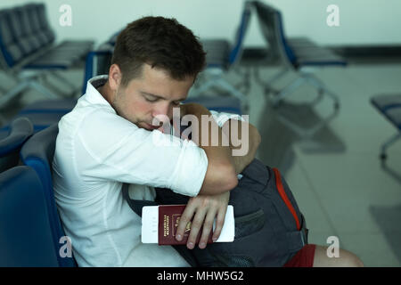 Caucasian man napping in airport. He is holding his passport and tickets. Russian Federation is written on document - Stock Photo
