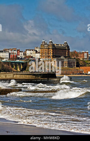 The Grand Hotel overlooks a high tide pushing waves against the sea defences in Scarborough's South Bay. - Stock Photo