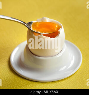 Soft-boiled egg in a porcelain egg cup with a little spoon on yellow background. - Stock Photo