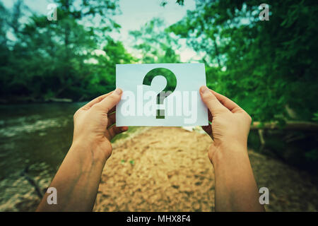 Close up of woman hands holding a paper sheet with the question mark inside, over green forest nature background. Lost people concept, global environm - Stock Photo