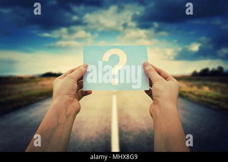 Close up of woman hands holding a paper sheet with the question mark inside, over asphalt road background. Lost people, business confusion concept, ch - Stock Photo