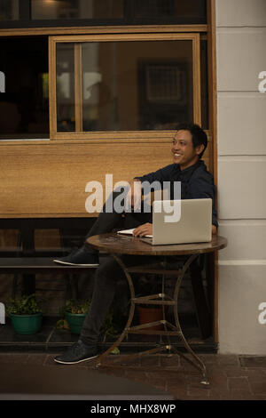 Businessman with laptop sitting in the pavement cafe - Stock Photo
