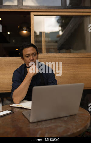 Thoughtful businessman looking at laptop - Stock Photo