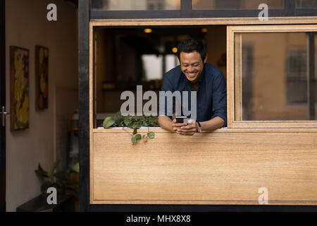 Businessman using mobile phone in the cafe - Stock Photo