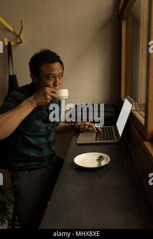 Businessman using laptop while having coffee - Stock Photo