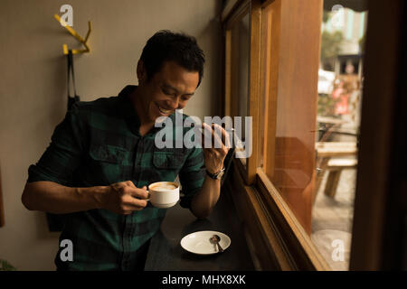 Businessman talking on mobile phone while having coffee in the cafe - Stock Photo