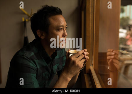 Thoughtful businessman having coffee - Stock Photo