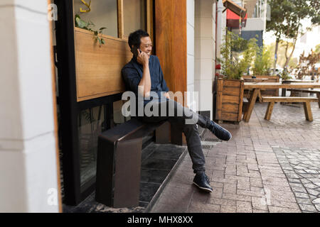 Businessman talking on phone in the pavement cafe - Stock Photo
