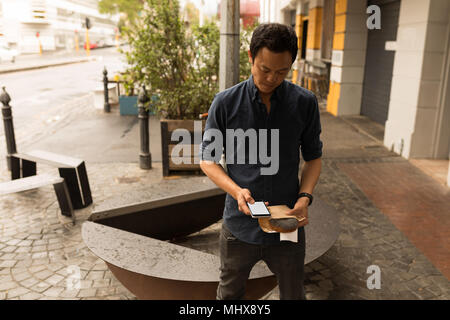 Businessman holding parcel while using mobile phone - Stock Photo