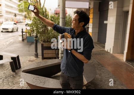 Businessman taking selfie with mobile phone - Stock Photo