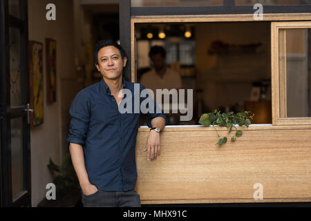 Businessman standing near window in the cafe - Stock Photo