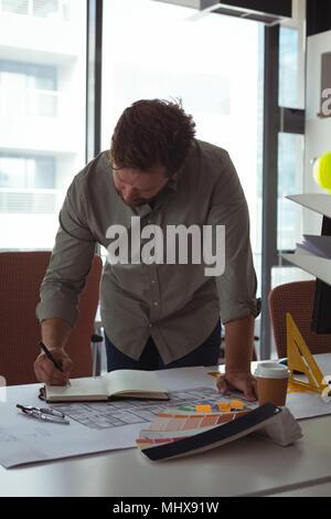 Architect writing note on diary - Stock Photo
