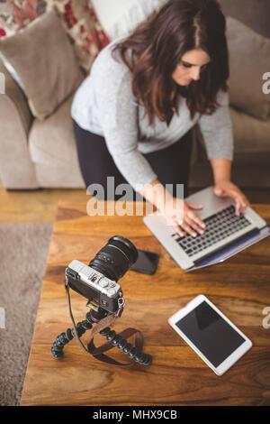 Female vlogger sitting on sofa while using laptop - Stock Photo