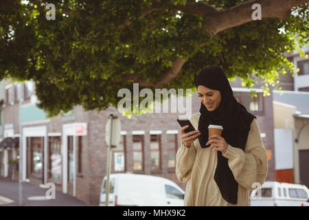 Hijab woman reviewing photos on mobile phone - Stock Photo
