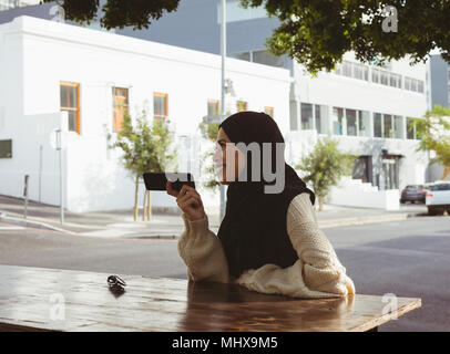 Urban hijab woman talking on mobile phone at pavement cafe - Stock Photo