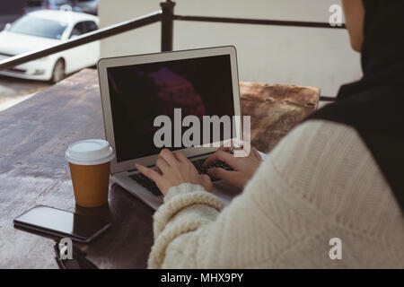 Urban hijab woman using laptop in pavement cafe - Stock Photo