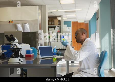 Scientist checking a chemical solution - Stock Photo