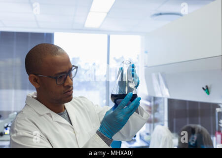 Scientist checking a solution in conical flask - Stock Photo