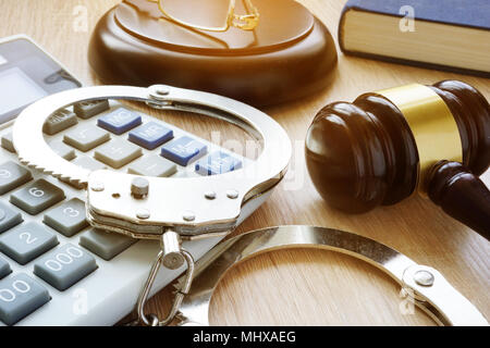 Handcuffs, gavel and calculator. Financial fraud. - Stock Photo