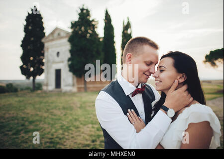 Happy stylish smiling couple walking and kissing in Tuscany, Italy on their wedding day. - Stock Photo