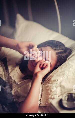 Girl rubbing eyes in bed - Stock Photo
