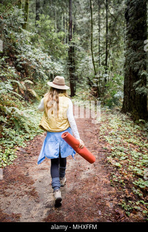 Young woman in trilby strolling in forest, rear view - Stock Photo
