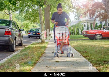 Mid adult woman pushing baby girl in pushchair on suburban sidewalk - Stock Photo