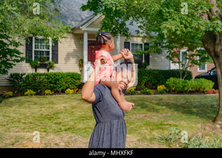 Mid adult woman in garden carrying baby daughter on shoulders, portrait - Stock Photo