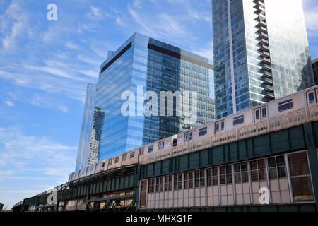 Subway train on elevated track passing skyscraper in Long Island City, New York City - Stock Photo
