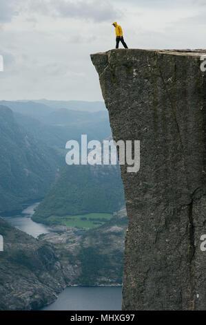 Nature photographer tourist standing on top of the mountain. Beautiful Nature Norway Preikestolen or Prekestolen. - Stock Photo