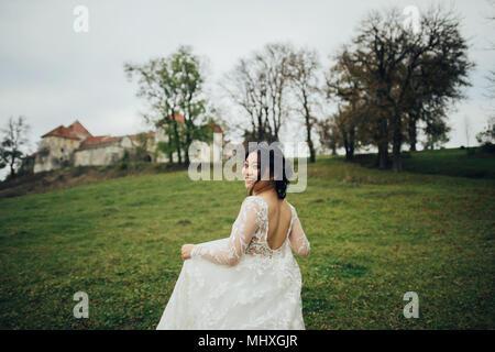Asian bride in elegant wedding dress running outdoor