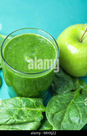 Glass with Green Fresh Smoothie from Leafy Greens Vegetables Fruits Bananas Kiwi Cucumber. Scattered Spinach Leaves Apple on Turquoise Background. Hea - Stock Photo