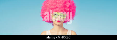 Portrait of beautiful woman in pink wig and green glasses with copy space - Stock Photo