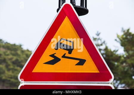 Slippery road, warning triangle road sign over bright sky background - Stock Photo