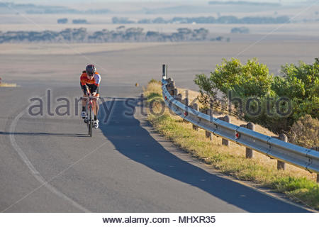 Female cyclist riding race bicycle on sunny open road - Stock Photo