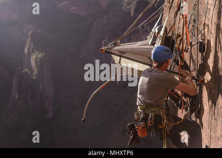 Two rock climbers attaching portaledge to rock, Liming, Yunnan Province, China - Stock Photo
