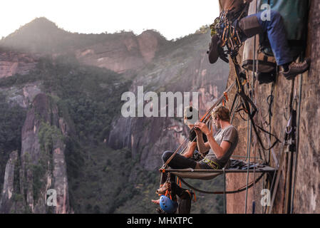 Two rock climbers sitting on portaledge, looking at view, Liming, Yunnan Province, China - Stock Photo