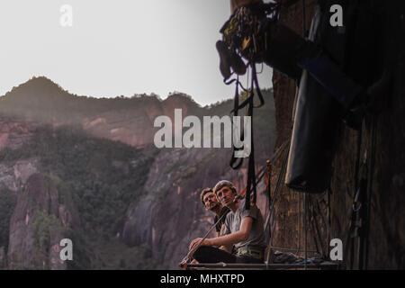 Two rock climbers sitting on portaledge, watching friend climb rock beside them, Liming, Yunnan Province, China - Stock Photo