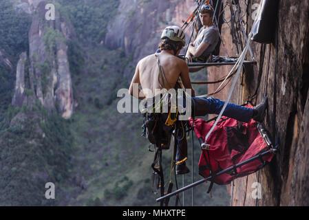 Rock climber securing portaledge, Liming, Yunnan Province, China - Stock Photo