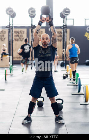 Man weightlifting with kettle bell in gym - Stock Photo