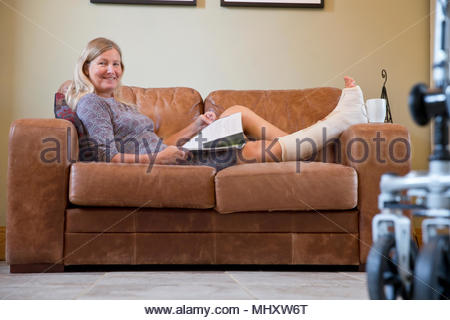Portrait Of Mature Woman With Leg In Plaster Cast Lying On Sofa At Home - Stock Photo
