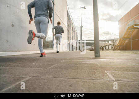 Young adult male twin runners, running along city sidewalk, rear view - Stock Photo